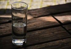 Vidrio de agua en piso de madera Fotos de archivo