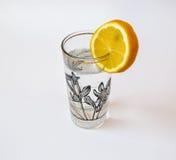 Vidrio de agua en un fondo blanco Fotos de archivo libres de regalías