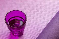 Vidrio de agua en una aptitud, estera de la yoga Forma de vida sana Imagen de archivo