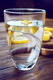Vidrio de agua mineral pura con el limón en la tabla de madera Imágenes de archivo libres de regalías