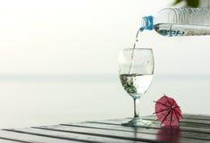 Vidrio de agua pura en una tabla oscura en la playa Fotos de archivo