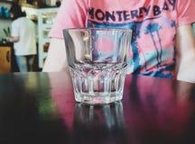 Vidrio de agua que se coloca en una tabla contra la perspectiva de la persona imágenes de archivo libres de regalías