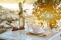 Vidrio de agua y café y gafas de sol en la tabla con al aire libre Foto de archivo