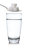 Vidrio de agua y de azúcar aislados en el fondo blanco fotos de archivo libres de regalías