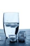 Vidrio de agua y de cubos de hielo de fusión en una tabla de madera Fotografía de archivo libre de regalías