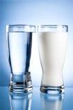 Vidrio de agua y de leche en un azul Imagen de archivo libre de regalías