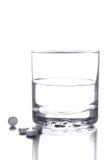 Vidrio de agua y de píldoras Foto de archivo libre de regalías