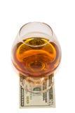 Vidrio de alcohol con el dólar Fotos de archivo libres de regalías