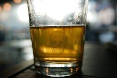 Vidrio de alcohol con el scull de la muerte en él Vidrio de cerveza Imagen de archivo