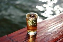 Vidrio de alcohol con hielo al lado del río imágenes de archivo libres de regalías