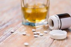 Vidrio de alcohol y de píldoras en la tabla fotografía de archivo