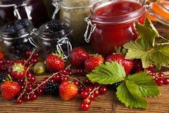 Vidrio de atasco mezclado de la baya con las fresas, arándanos, curr rojo Foto de archivo
