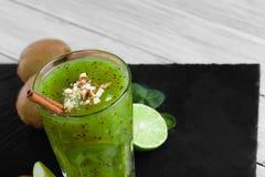 Vidrio de batido de leche hecho en casa del kiwi y de la cal Primer de un smoothie verde Postre y frutas dulces en un fondo liger Imagenes de archivo