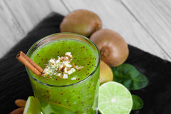 Vidrio de batido de leche hecho en casa del kiwi y de la cal Primer de un smoothie verde Postre y frutas dulces en un fondo liger Fotografía de archivo