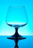 Vidrio de brandy aislado en fondo azul Imagen de archivo libre de regalías