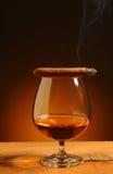 Vidrio de brandy con el cigarro Imagen de archivo libre de regalías