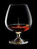 Vidrio de brandy con gotas y chapoteo en negro Fotos de archivo