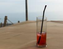 Vidrio de cóctel con una bebida roja fría con cubos de hielo y una paja, Foto de archivo
