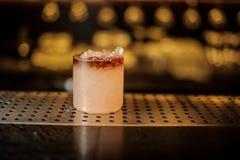 Vidrio de cóctel elegante llenado de la bebida alcohólica dulce sabrosa con hielo fotos de archivo