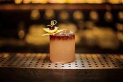 Vidrio de cóctel elegante llenado de la bebida alcohólica dulce sabrosa con las rebanadas del hielo y de la fruta foto de archivo libre de regalías