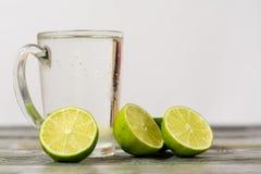 Vidrio de cal y un vidrio de la bebida en una tabla de madera Fotografía de archivo libre de regalías
