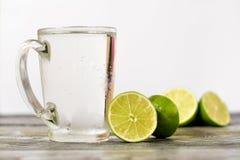 Vidrio de cal y un vidrio de la bebida en una tabla de madera Fotos de archivo libres de regalías