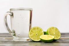 Vidrio de cal y un vidrio de la bebida en una tabla de madera Foto de archivo libre de regalías
