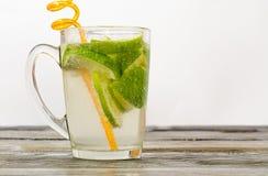 Vidrio de cal y un vidrio de la bebida en una tabla de madera Imagen de archivo
