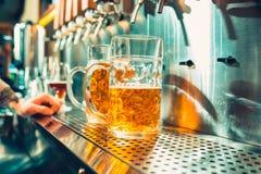 Vidrio de cerveza con el barril, la botella y la aún-vida fresca de los saltos Fotos de archivo