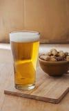 Vidrio de cerveza con el cacahuete en fondo de madera Fotos de archivo libres de regalías