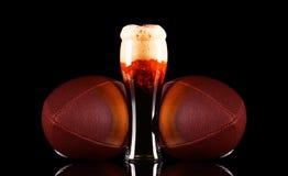 Vidrio de cerveza con espuma de la cerveza oscura y bola del fútbol americano en fondo negro Imagen de archivo libre de regalías