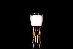 Vidrio de cerveza con espuma en fondo negro Foto de archivo