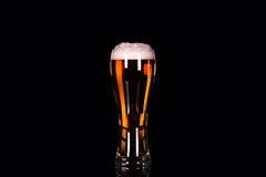 Vidrio de cerveza con espuma en fondo negro Imagen de archivo libre de regalías