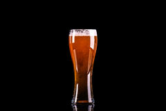 Vidrio de cerveza con espuma en fondo negro Fotos de archivo libres de regalías