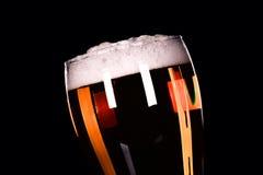 Vidrio de cerveza con espuma en fondo negro Fotos de archivo