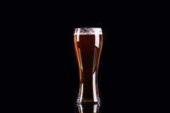 Vidrio de cerveza con espuma en fondo negro Imagen de archivo