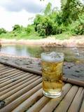 Vidrio de cerveza con hielo en la tabla de bambú Foto de archivo