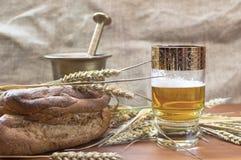 Vidrio de cerveza con la cebada en la tabla Fotografía de archivo