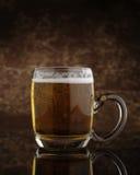 Vidrio de cerveza con la maneta Imagen de archivo