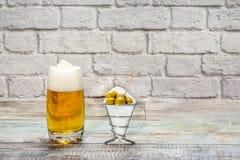Vidrio de cerveza con las aceitunas verdes Imagen de archivo