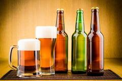 Vidrio de cerveza con las botellas foto de archivo