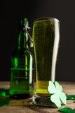 Vidrio de cerveza, de botella de cerveza y de los tréboles verdes para el día del St Patricks Imagen de archivo