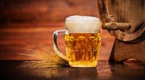 Vidrio de cerveza dorada con el barrilete de madera viejo Imagenes de archivo