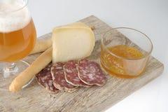 Vidrio de cerveza dorada con queso Fotografía de archivo libre de regalías