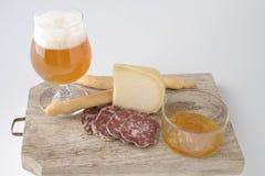 Vidrio de cerveza dorada con queso Foto de archivo libre de regalías