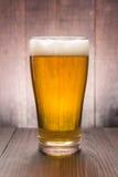 Vidrio de cerveza en el fondo de madera Foto de archivo libre de regalías