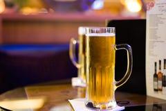 Vidrio de cerveza en la tabla de la barra foto de archivo