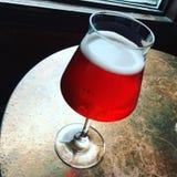 Vidrio de cerveza estacional de la cereza en una tabla de la barra imagenes de archivo