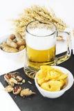 Vidrio de cerveza fría con los microprocesadores y los cacahuetes aislados en la parte posterior del blanco Imagen de archivo