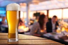 Vidrio de cerveza fría en la tabla de la barra Imagen de archivo